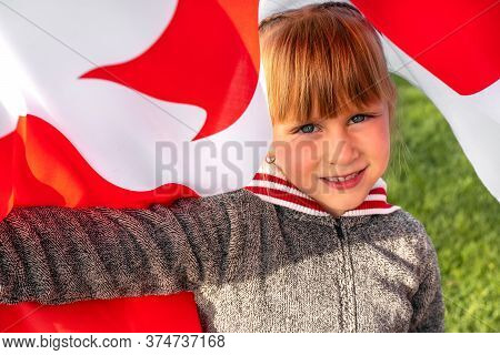 Happy Canada Day Celebration Concept. Pretty Cute Young Caucasian Girl Close Up Portrait Is Holding