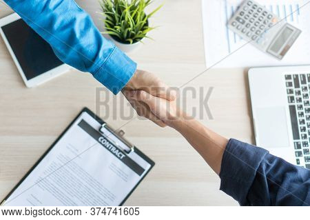 Top View Customer And Insurance Agent Shaking Hands Over Investment Plan Document And Calculator As