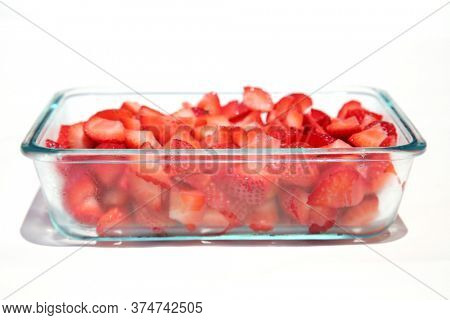 Strawberries. Strawberries diced into small pieces in a glass baking dish. Isolated on white. Room for text. Strawberries are enjoyed by Humans and Animals World Wide.