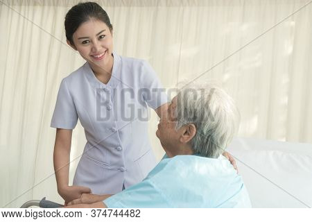 Cheerful Asian Nurse Visiting Elderly Patient To Check Up After Surgery In Hospital For Giving Physi