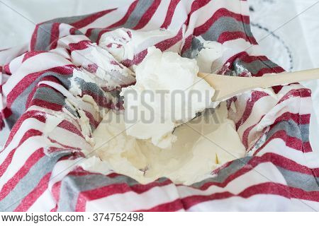 Spoonful Of Fresh Home Made Labneh Still In Cloth With Wooden Spoon