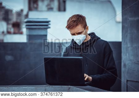 young guy with a laptop during a pandemic