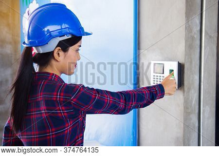 Woman Employee Scanning Fingerprint On The Machine To Record Working Time.