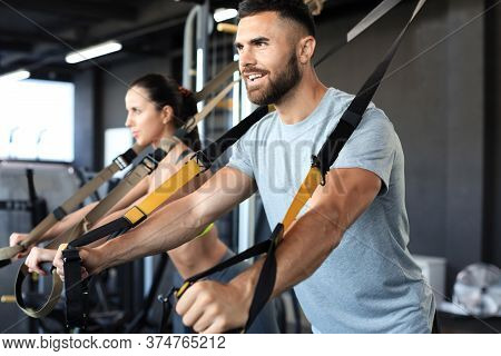 Young Couple On Body Training With Trx In Gym.