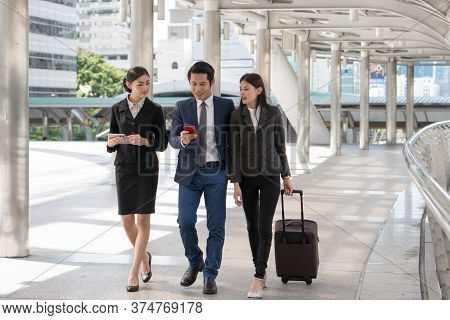 Group Of Business People Checking Flight From Mobile Phone During Walk To Check In At Airport. Boss