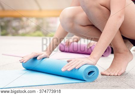 Woman Roll Out Yoga Mat And Preparing To Meditate Training In Yoga Class Session With Her Friend.