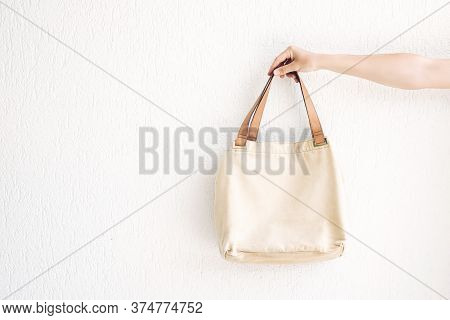 Hand Holding Rcraft Linen Eco Bag For Food Or Lunch On White  Wall Background. Eco-friendly Concept