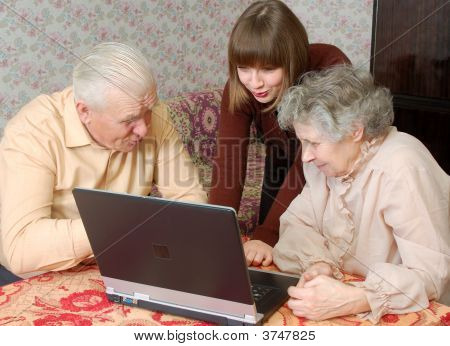 Grandparents And Granddaughter Looking To The Laptop