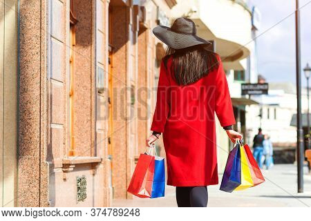 Woman With Shopping Bags Walking Out From Shop. Fashion, Lifestyle And Shopping. Shopaholic Lady Aft