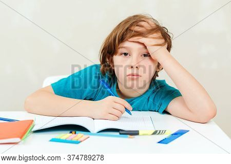 Tired Schoolboy Sitting At Table. Boy Doing Homework. Learning Difficulties, Education Concept. Stre