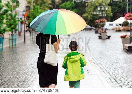 Summer Day With Rain. Happy Family On A Walk During Rainy Weather. Mother With Big Colorful Rainbow