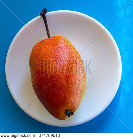 Pear Lies In A White Plate On A Blue Background. Summer Season.