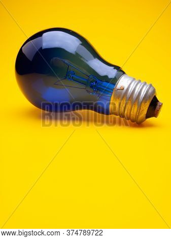 Blue Incandescent Lamp Lies On A Yellow Background. Web Banner. Business Concept.