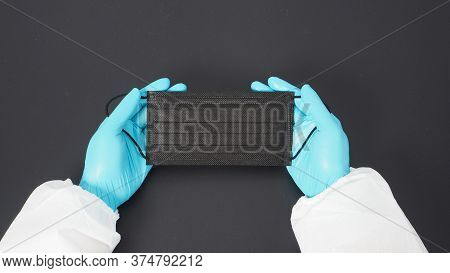Two Hand Wear Ppe Suite And Gloves And Holding Black Face Mask. Put On Black Background.