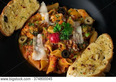 Penne Pasta In Tomato Sauce With Chicken, Tomatoes Decorated With Parsley On A Wooden Table, Penne P