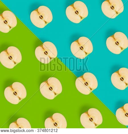Creative layout over colorfool background. Fruit pattern. Apple halves geometrical layout. Flat lay, top view. Food background..  Pop art design, creative summer concept.