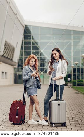 Two Cute Young Women Searching Location On Cell Phone In Airport. Women Arrived On Vacation With Sma