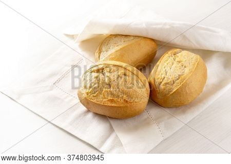 Fresh Bread Rolls Or Buns In A White Napkin For Breakfast On The Table, Copy Space, Selected Focus,