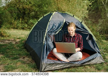 Woman Working On Laptop In Tent In Nature. Young Freelancer Sitting In Camp. Relaxing In Camping Sit