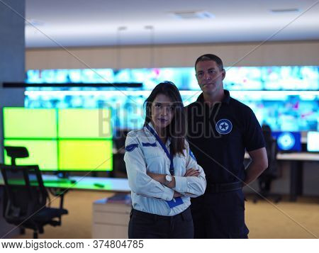 portrait of male and female security operator while working in a data system control room offices Technical Operator Working at  workstation with multiple displays, security guard working on multiple