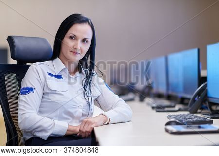 portrait of female security operator while working in a data system control room offices Technical Operator Working at  workstation with multiple displays, security guard working on multiple monitors