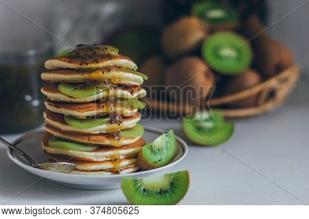 Plate Of Pancakes Dripping With Kiwi Jam With Kiwi Pieces. Shrovetide Maslenitsa Butter Week Festiva