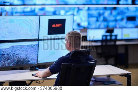 Male security operator working in a data system control room offices Technical Operator Working at  workstation with multiple displays, security guard working on multiple monitors  Male computer opera