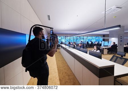 Professional videographer with gimball video slr recording video of Security data center operators while working in a CCTV monitoring room looking on multiple monitors   Team working on the System Co