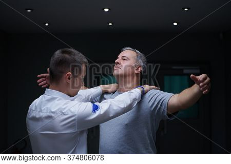 Security guard making body searching procedure on man for finding hidden objects before entering in treasury department