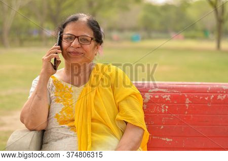 Senior Indian Woman Speaking On Her Smart Phone, Sitting On A Red Bench In A Park In New Delhi. Conc