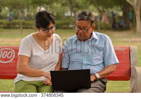 Young Indian Woman Manager In Western Formals / Shirt Helping Old Indian Man On A Laptop Promoting D