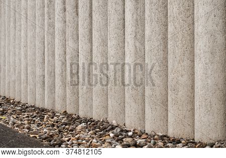 A Garden Wall Of Rough Cement Columns With Pebbles As Drainage Material Next To It
