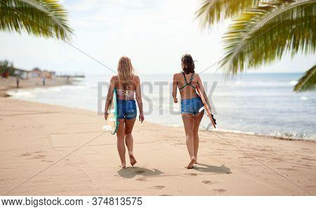 Young sexy female surfers enjoying walk a beautiful  beach