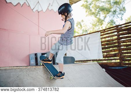 Caucasian Boy In A Helmet Does Tricks On A Skateboard On A Playground For Skateboarding Outside. A C