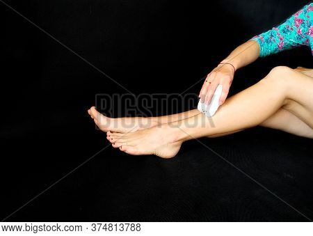 Girl In Makes Hair Removal At Home With White Epilator On Legs At Home. Isolated On Black. Selfcare