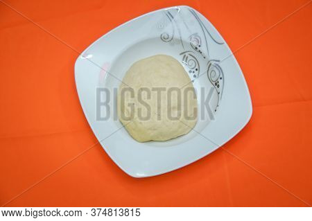 Raw Dough Lying On The Plate On A White Background. A Piece Of Dough For Bread Baking . The Dough Is