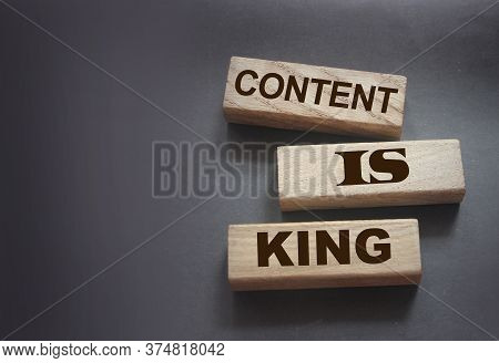 Content Is King Words Printed On Wooden Blocks On Dark Grey Background. Seo Marketing Strategy Busin