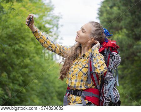 Hiker Woman Make A Selfie With Mobile Phone. Woman Trekker Taking A Photo.