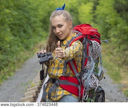 Hiker Woman With Binokular Looking At Camera And Keeping Thumb Up. Lifestyle Travel Portrait.