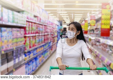 Asian Woman Wear Face Mask Push Shopping Cart In Supermarket. Girl Looking Grocery To Buy  Something