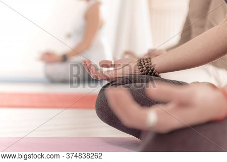Close-up Of Feminine And Masculine Arms And Crossed Legs During Meditation. How To Keep Your Arms In