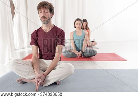 Yoga Teachers Sitting In The Lotus Position With Their Eyes Closed. Group Of People Practicing Yoga.