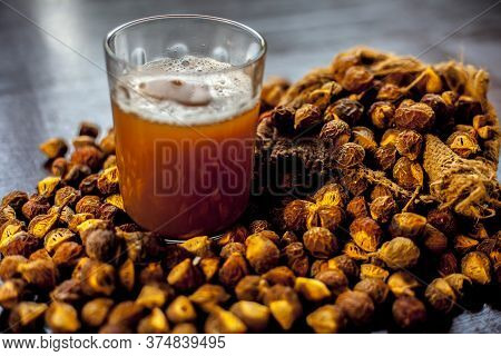 Close Up Shot Of Fresh Raw Soapnut On Brown Surface Along With Its Solution Or Liquid In A Glass Alo