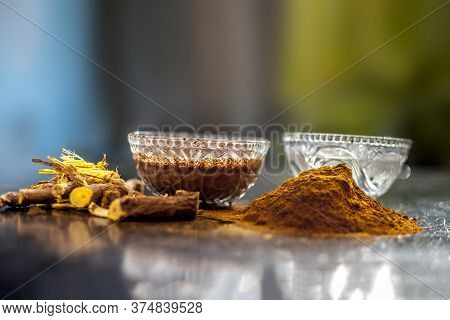 Close Up Of Raw Revand Chini Along With Its Powder And Some Lukewarm Water With It On A Black Wooden