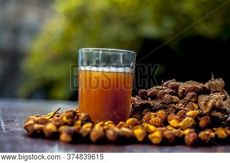 Close Up Shot Of Fresh Raw Soapnut On The Brown Surface Along With Its Solution Or Liquid In A Glass
