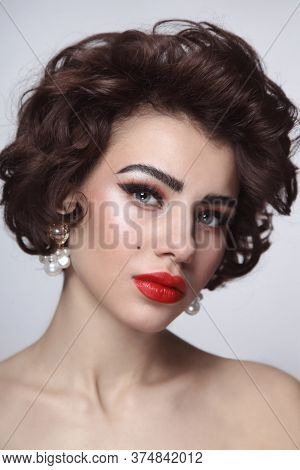 Vintage style portrait of young beautiful woman with glamorous makeup