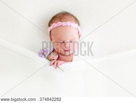 Sleeping newborn baby girl with flowers wrapped in white blanket