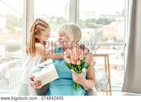 Smiling granny with presents from cute granddaughter in bright room