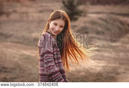 Attractive girl with sun in fluttering hair on nature background