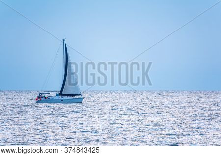 Sailing Yacht In The Blue Calm Sea. Yacht In Peaceful Waters.